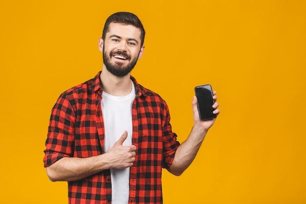Portret uśmiechnięty atrakcyjny mężczyzna trzyma pustego ekranu telefon komórkowego i pokazuje aprobata gest odizolowywającego nad kolor żółty ścianą.