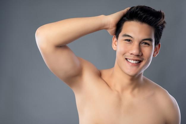 Portret uśmiechnięty bez koszuli młody przystojny azjatycki mężczyzna z ręką w włosy