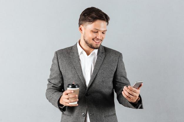 Portret uśmiechnięty biznesmen patrzeje telefon komórkowego