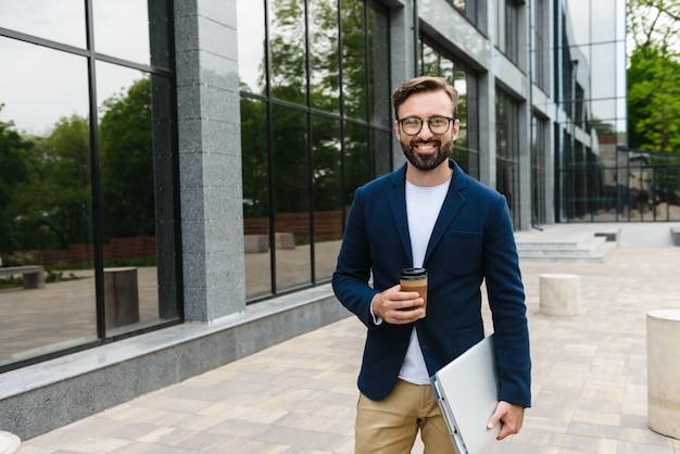 Portret uśmiechnięty biznesmen w okularach, trzymając laptop i papierowy kubek podczas spaceru na zewnątrz w pobliżu budynku
