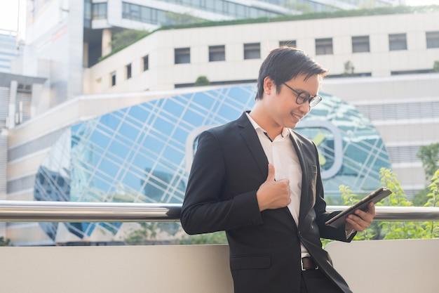 Portret uśmiechnięty biznesowego mężczyzna spojrzenie ufny używa komputerową pastylkę
