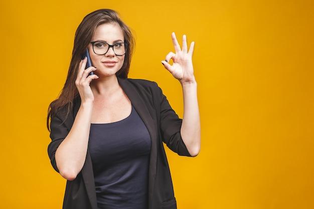 Portret uśmiechnięty biznesowej kobiety telefon opowiada i pokazuje ok odizolowywa przeciw kolor żółty ścianie.