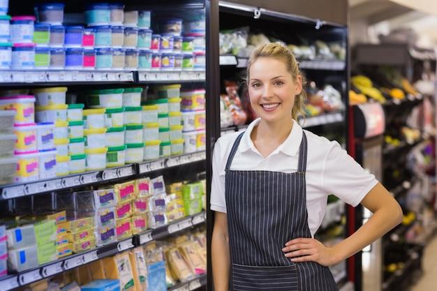 Portret uśmiechnięty blondynka pracownik z ręką na biodrze