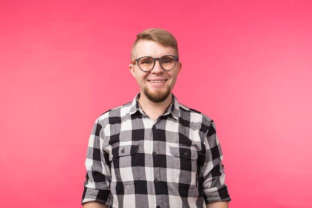 Portret uśmiechnięty brodaty mężczyzna w okularach patrząc na kamery na białym tle nad różową powierzchnią