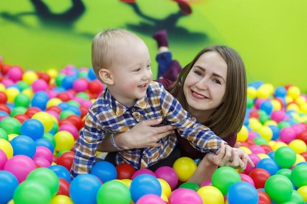 Portret uśmiechnięty chłopiec gra w centrum gry z matką. zabawny chłopak w basenie z wielokolorowe kulki. mama i syn bawią się razem w pokoju zabaw z bliska. szczęśliwe dzieciństwo. rodzinny weekend.