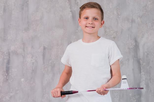 Portret uśmiechnięty chłopiec mienia rakieta i wolant patrzeje kamerę