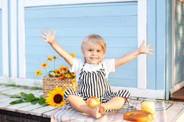 Portret uśmiechnięty chłopiec obsiadanie na drewnianym ganeczku w domu na jesień dniu. koncepcja dzieciństwa. dziecko bawi się na podwórku jesienią. wesołe dziecko. żniwny. mały rolnik. urocze dziecko