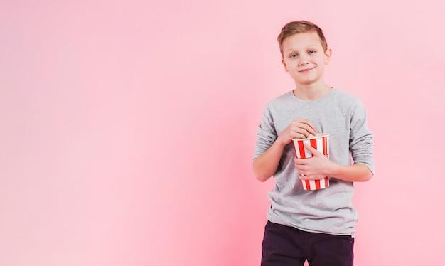 Portret uśmiechnięty chłopiec trzyma wiadro popcornu na różowym tle