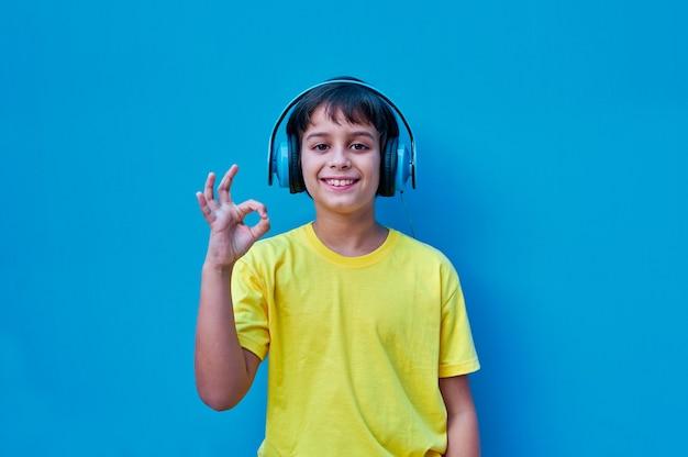 Portret uśmiechnięty chłopiec w żółtej koszulce i niebieskich słuchawkach robi ok gest ręką
