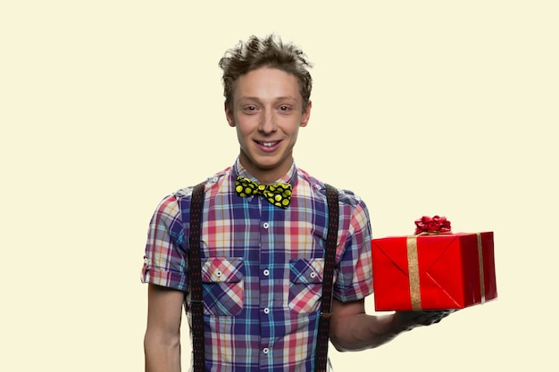 Portret uśmiechnięty chłopiec z muszką trzyma czerwone pudełko. szczęśliwy uczeń z muszką na białym tle.