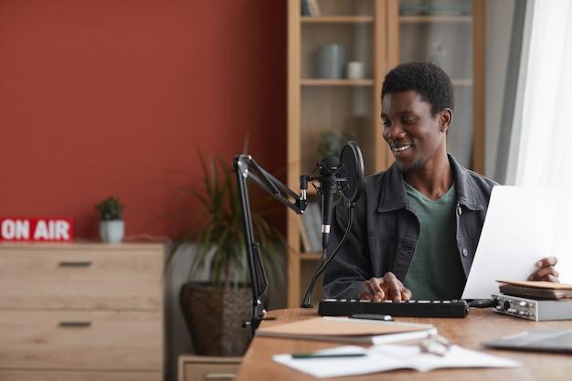 Portret uśmiechnięty człowiek african-american śpiewa do mikrofonu podczas nagrywania muzyki w domowym studio, kopia przestrzeń