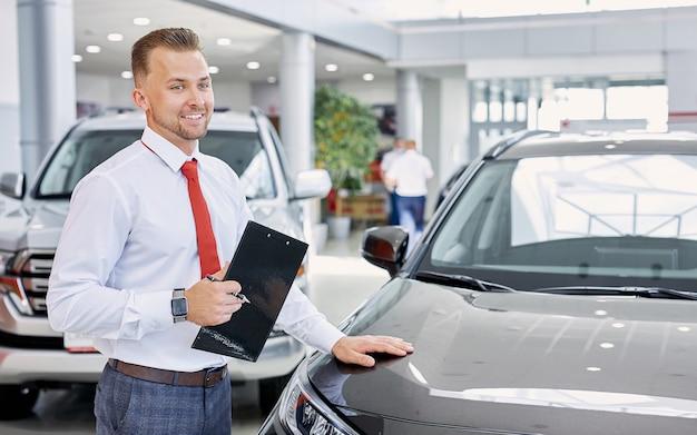 Portret uśmiechnięty dealer samochodowy w pracy