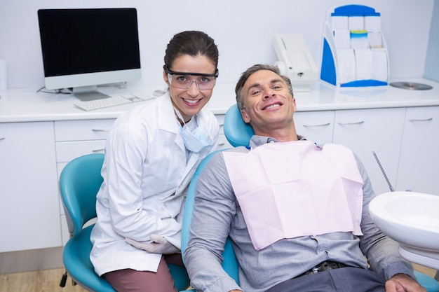Portret uśmiechnięty dentysta i pacjent siedzi na krześle