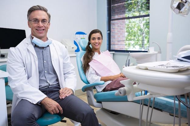 Portret uśmiechnięty dentysta i pacjent stojący na krześle