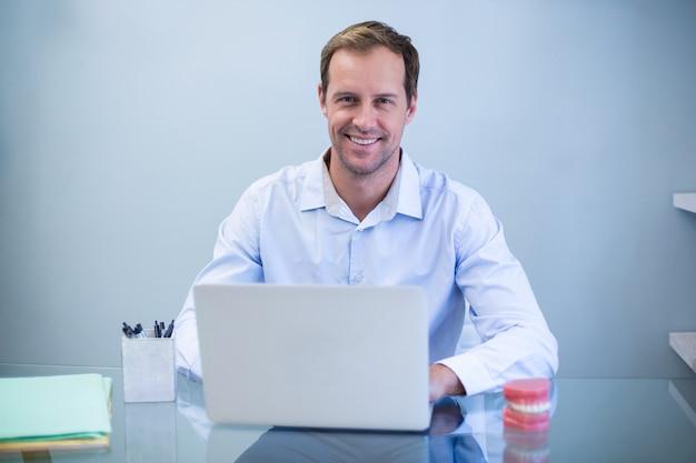 Portret uśmiechnięty dentysta pracuje na laptopie