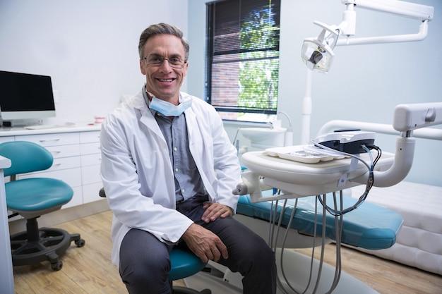 Portret uśmiechnięty dentysta siedzi na krześle