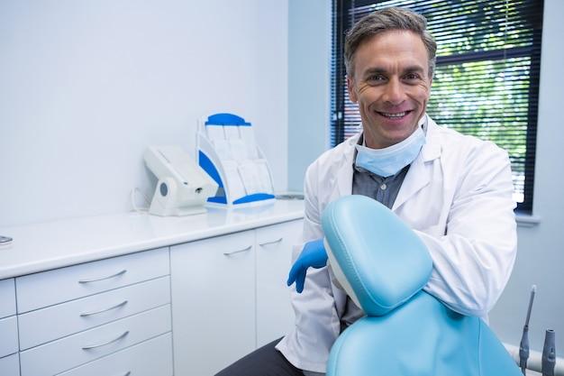 Portret uśmiechnięty dentysta stojący przy krześle