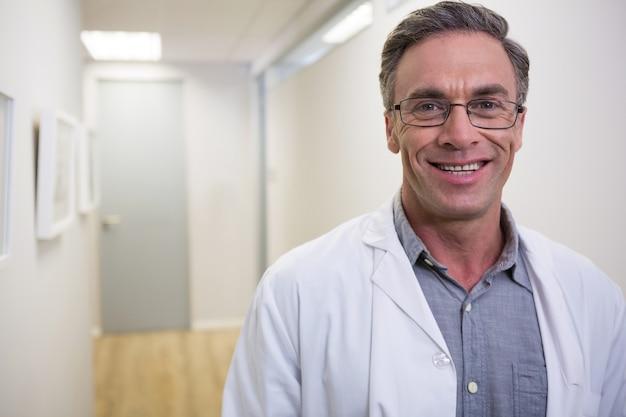 Portret uśmiechnięty dentysta stojący w holu