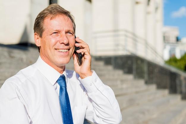 Portret uśmiechnięty dojrzały biznesmen opowiada na telefonie komórkowym