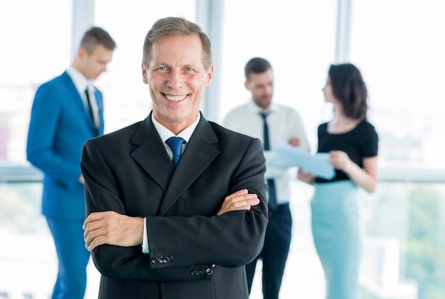Portret uśmiechnięty dojrzały biznesmen z fałdowymi rękami
