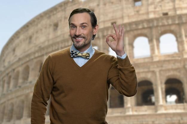 Portret uśmiechnięty dojrzały mężczyzna pokazuje ok gest. przystojny turysta kaukaski w średnim wieku. koloseum w tle.