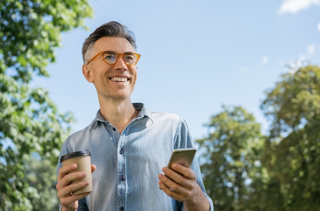 Portret uśmiechnięty dojrzały mężczyzna ubrany w stylowe okulary spaceru w parku