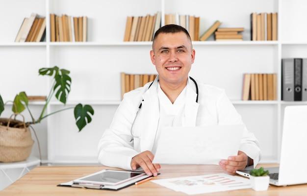 Portret uśmiechnięty doktorski obsiadanie na biurku