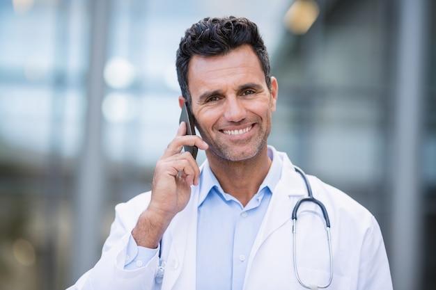 Portret uśmiechnięty doktorski opowiadać na telefonie komórkowym