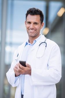 Portret uśmiechnięty doktorski używa telefon komórkowy