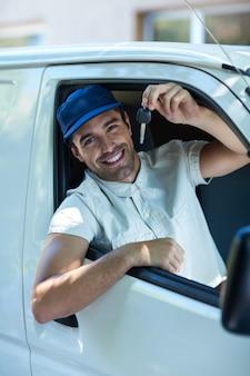 Portret uśmiechnięty doręczeniowy mężczyzna pokazuje samochodów klucze