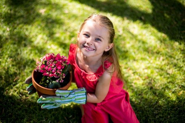 Portret uśmiechnięty dziewczyny mienia kwiatu garnek w jardzie