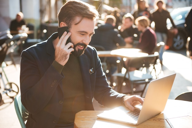 Portret uśmiechnięty elegancki mężczyzna pracuje na laptopie