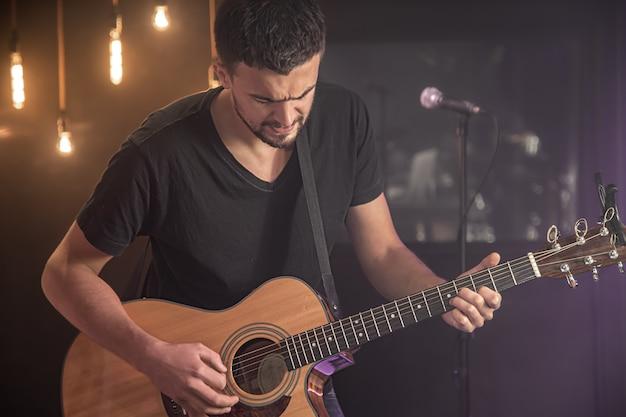 Portret uśmiechnięty gitarzysta w czarnej koszulce gra na gitarze akustycznej na niewyraźne studio ciemnej przestrzeni.