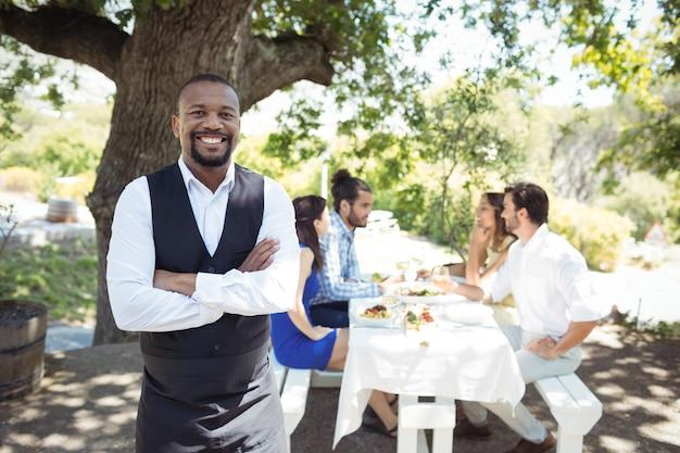 Portret uśmiechnięty kelner stojący z rękami skrzyżowanymi