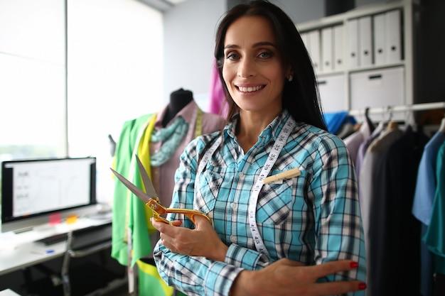 Portret uśmiechnięty kobieta krawczyna stoi blisko wygodnego miejsca pracy