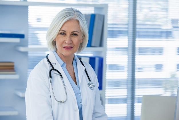 Portret uśmiechnięty kobiety lekarki obsiadanie przy biurkiem