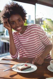 Portret uśmiechnięty kobiety obsiadanie w kawiarni