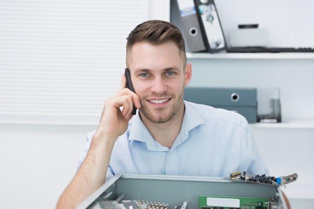 Portret uśmiechnięty komputerowy inżynier na wezwaniu przed otwartą jednostką centralną