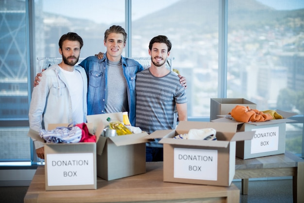 Portret uśmiechnięty kreatywny biznes zespół stojący z pudełkiem darowizn w biurze