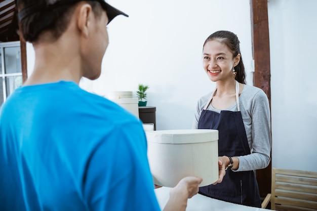 Portret uśmiechnięty kurier przynosi paczkę dla młodej sklepikarki odbierającej paczkę od kuriera