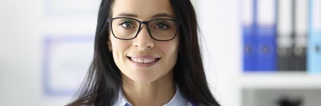 Portret uśmiechnięty lekarz w okularach w koncepcji opieki medycznej i usług medycznych w gabinecie medycznym