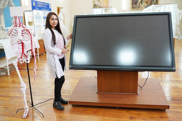 Portret uśmiechnięty lekarz w pobliżu dużego ekranu komputera