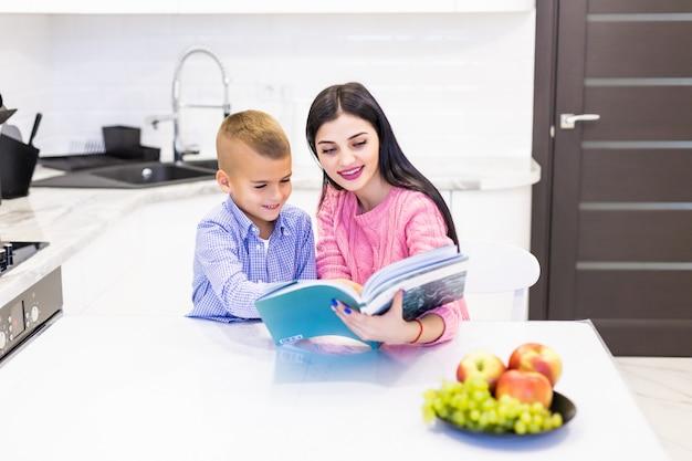 Portret uśmiechnięty macierzysty pomaga syn z pracą domową i mieć dobrego czas w kuchni