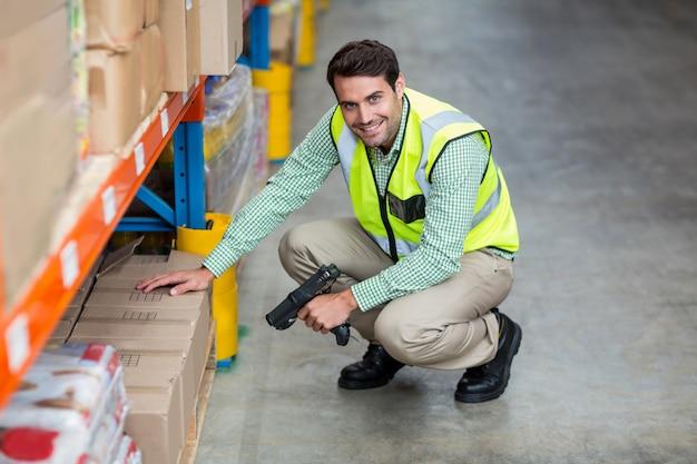 Portret uśmiechnięty magazynu pracownika skanerowania pudełko