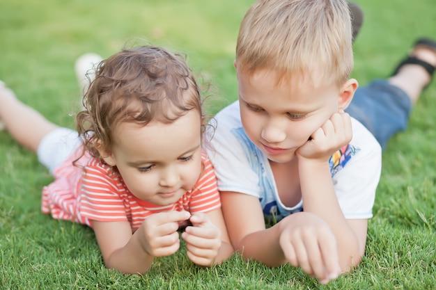 Portret uśmiechnięty małej dziewczynki i chłopiec lying on the beach na zielonej trawie.