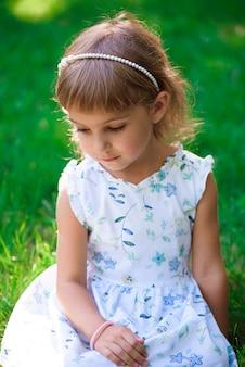 Portret uśmiechnięty małej dziewczynki obsiadanie na zielonej trawie.