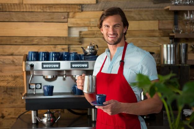 Portret uśmiechnięty męski barista parzenia kawy w kawiarni