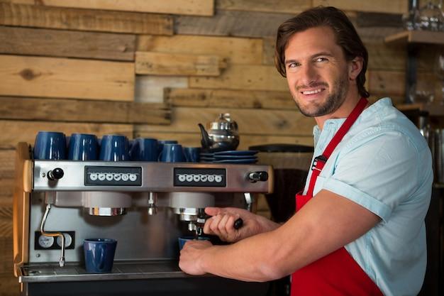Portret uśmiechnięty męski barista przygotowuje kawę z maszyną w kawiarni