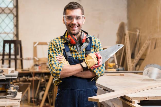 Portret uśmiechnięty męski cieśli mienia handsaw patrzeje kamerę