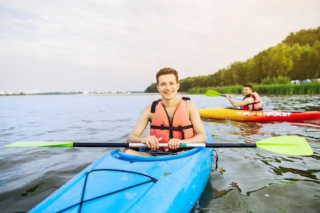 Portret uśmiechnięty męski kajakarz kayaking na jeziorze